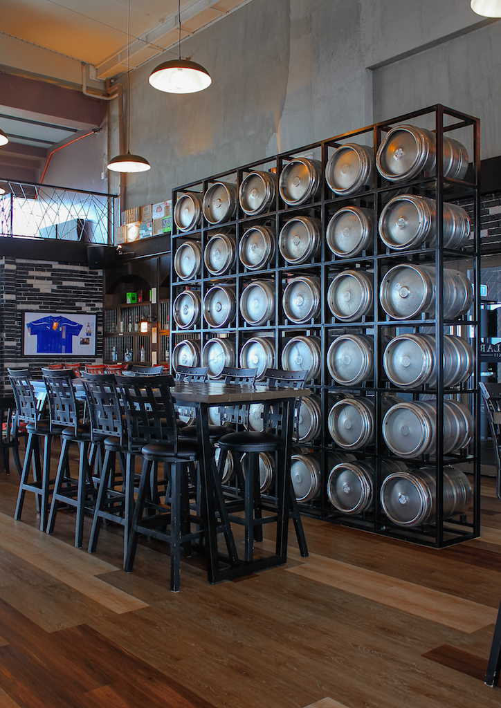 At the center of the bar, there is a wall made out of beer kegs